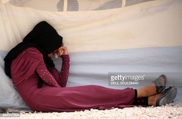 A displaced Syrian woman who fled the Islamic State group stronghold of Raqa sits at a temporary camp in the northern Syrian village of Ain Issa on...