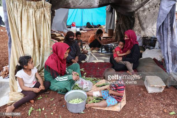 Displaced Syrian women prepare Iftar meal in a field near a camp for displaced people at the village of Atme in the jihadistheld northern Idlib...