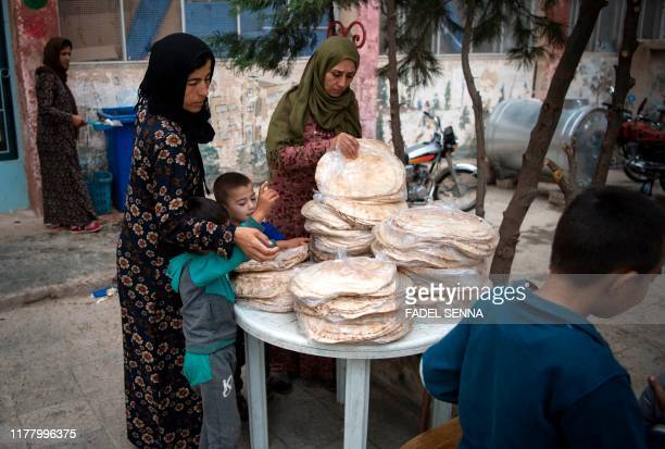 Displaced Syrian women take bread at a school turned into a shelter for people displaced by the war in the northeastern Syrian town of Hasakeh on...