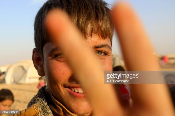 A displaced Syrian youth from Deir Ezzor gestures to the camera at a camp for internally displaced people in Ain Issa on October 21 2017 / AFP PHOTO...