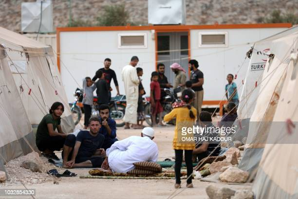Displaced syrians chat in the camp 'Hope' in the Syrian village of Kafr Lusein north of the Bab alHawa border crossing on September 13 2018