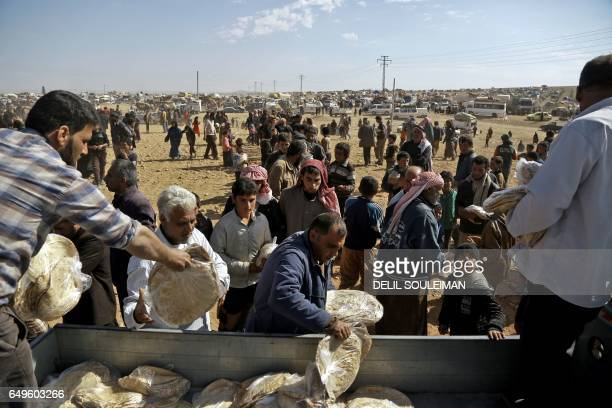 Displaced Syrians collect aid food at a makeshift camp for displaced people near the northern town of Manbij on March 8 2017 Tens of thousands of...