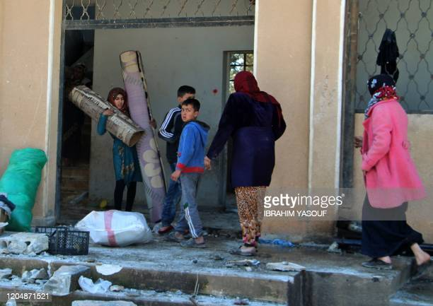 Displaced Syrians collect belongings from a school that was reportedly targeted in a regime forces' air strike in Syria's northwestern Idlib province...