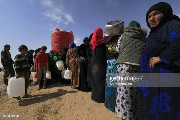 Displaced Syrians collect water from a tank at a camp housing people who fled the fighting in Deir Ezzor Mayadeen and Albu Kamal on October 14 in the...