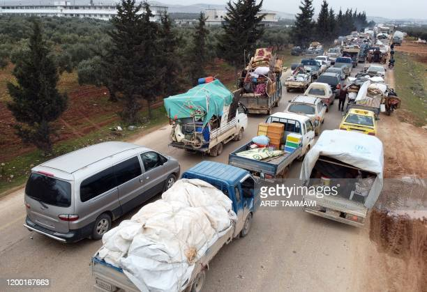 Displaced Syrians drive through the town of Hazano in Idlib's northern countryside, on February 11 as people flee an ongoing pro-regime offensive. -...