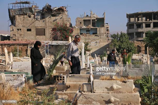 TOPSHOT Displaced Syrians from Jobar now living in eastern Ghouta visit graves in a destroyed cemetary their in hometown on the first day of the...