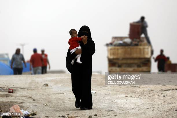 Displaced Syrians from the eastern city of Deir Ezzor and Raqa who were forced to leave by the war against the Islamic State group are pictured...