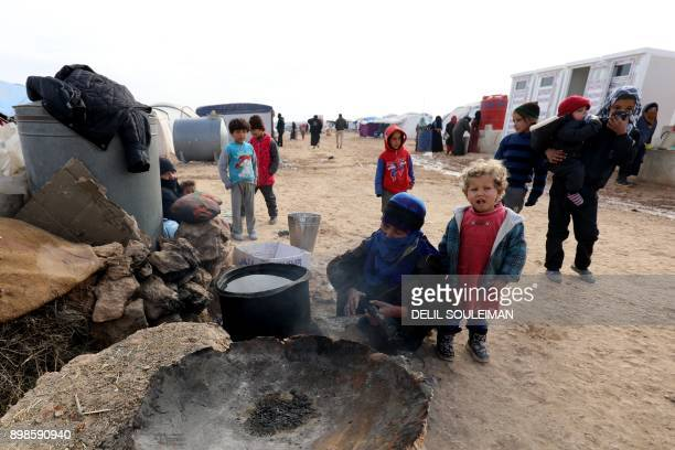 Displaced Syrians from the eastern city of Deir Ezzor and Raqa who were forced to leave by the war against the Islamic State group prepare food at...