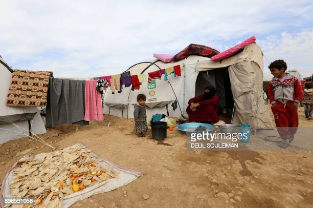 Displaced Syrians from the eastern city of Deir Ezzor and Raqa who were forced to leave by the war against the Islamic State group are seen outside a...