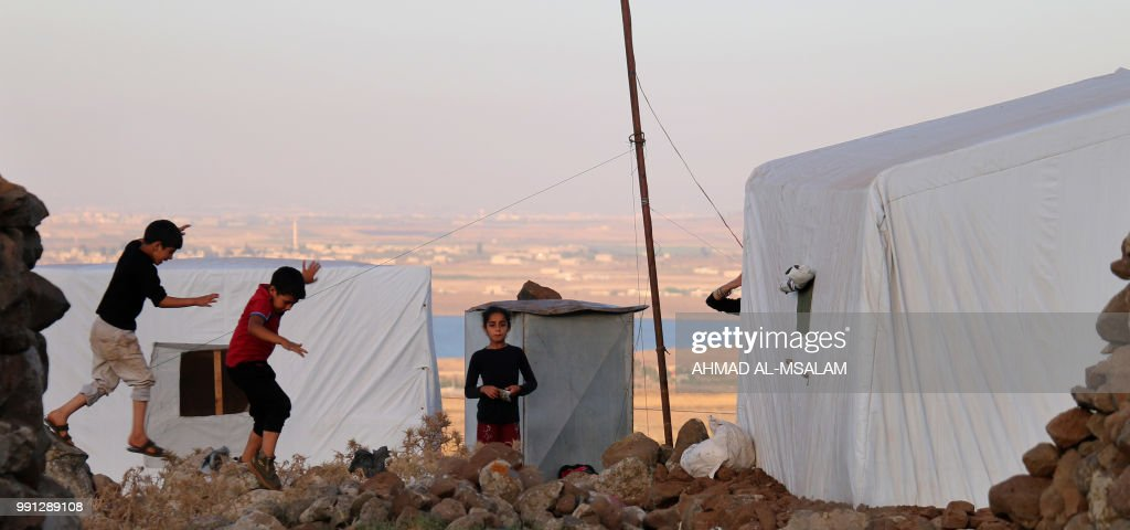 Displaced Syrians from the province of Daraa are seen in a makeshift camp in the area of the village of Burayqah near the border between the Israeli-occupied Golan heights and Syria on July 3, 2018. - Tens of thousands of Syrians have fled since the beginning of the offensive by Syrian government forcesand the Syrian Observatory for Human Rights monitoring group says that nearly 100 civilians have been killed. (Photo by Ahmad al-Msalam / AFP) / The erroneous mention appearing in the metadata of this photo by Ahmad al-Msalam has been modified in AFP systems in the following manner: PICTURES WERE TAKEN AT A CAMP IN SYRIA'S QUNEITRA PROVINCE instead of AT CAMP IN NASIB NEAR THE JORDANIAN BORDER. Please immediately remove the erroneous mention[s] from all your online services and delete it from your servers. If you have been authorized by AFP to distribute it to third parties, please ensure that the same actions are carried out by them. Failure to promptly comply with these instructions will entail liability on your part for any continued or post notification usage. Therefore we thank you very much for all your attention and prompt action. We are sorry for the inconvenience this notification may cause and remain at your disposal for any further information you may require.