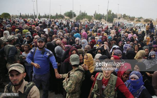 Displaced Syrians gather to receive aid boxes provided by the Turkish Red Crescent on October 19 in the Syrian border town of of Tal Abyad which was...