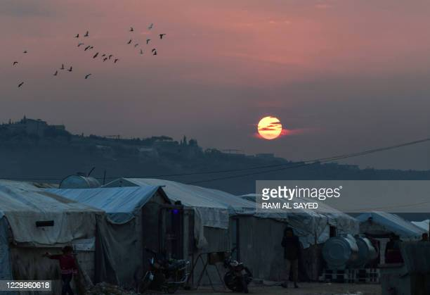 Displaced Syrians go about their lives as the sun sets at a camp near Deir al-Ballut town in Afrin's countryside, in Syria's Aleppo province near the...