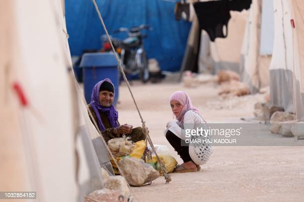 Displaced syrians pose for a photograph in the camp 'Hope' in the Syrian village of Kafr Lusein north of the Bab alHawa border crossing on September...