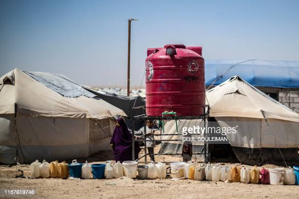 Displaced Syrians queue for water next to a tank at alHol camp for the internally displaced people in alHasakeh governorate in northeastern Syria on...