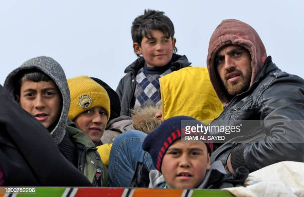 Displaced Syrians ride in the back of a truck as they pass by Dayr Ballut on their way to Afrin and Azaz near the Turkish border in the rebel-held...