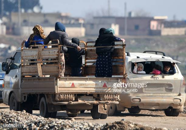 Displaced Syrians ride in trucks and cars as they pass by Dayr Ballut on their way to Afrin and Azaz near the Turkish border in the rebel-held part...