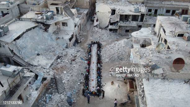 TOPSHOT Displaced Syrians sit amid the ruins of their destroyed neighbourhood as they break their fast during an Iftar meal organised by a local...