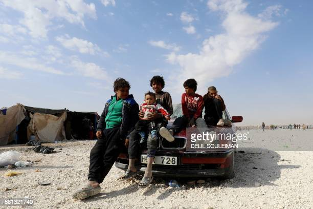 Displaced Syrians sit in a car at a camp housing people who fled the fighting in Deir Ezzor Mayadeen and Albu Kamal on October 14 in the town of...