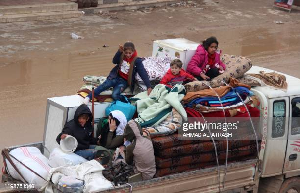 Displaced Syrians sit in the back of a truck loaded with belongings passing through the town of Hazano in Idlib's northern countryside on February 5...