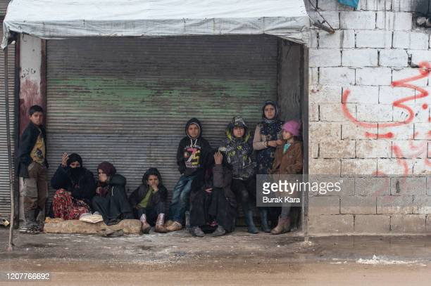 Displaced Syrians wait in front of a closed shop on February 21, 2020 in Idlib, Syria. Turkey's President Recep Tayyip Erdogan in a speech Tuesday...