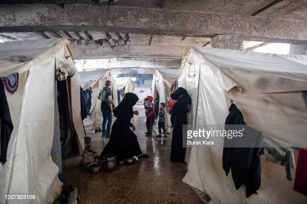 Displaced Syrians wait in front of their tents at the basement of a stadiums tribunes as it is turned into a makeshift refugee shelter on February...