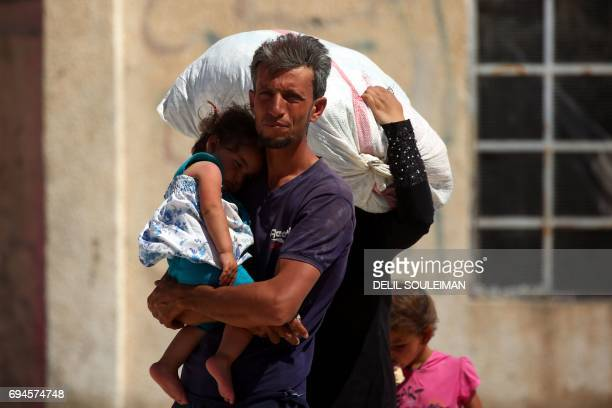 Displaced Syrians walk at a temporary camp in the northern Syrian village of Ain Issa on June 10 where many people who fled the Islamic State group...