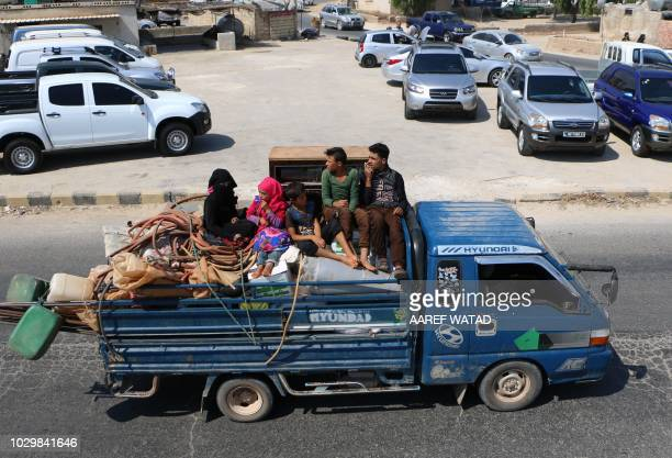 Displaced Syrians who fled from regime raids ride in a truck with their belongings arrive near a camp in Kafr Lusin near the border with Turkey in...