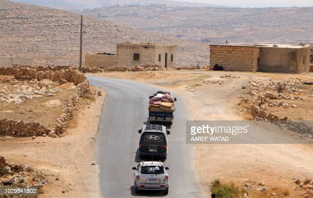 Displaced Syrians who fled from regime raids ride in vehicles with their belongings arrive near a camp in Kafr Lusin near the border with Turkey in...