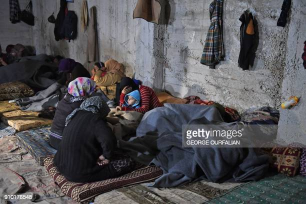 TOPSHOT Displaced Syrians who fled from the town of Jandairis in the southwestern corner of the Afrin border enclave where Turkey and allied rebels...