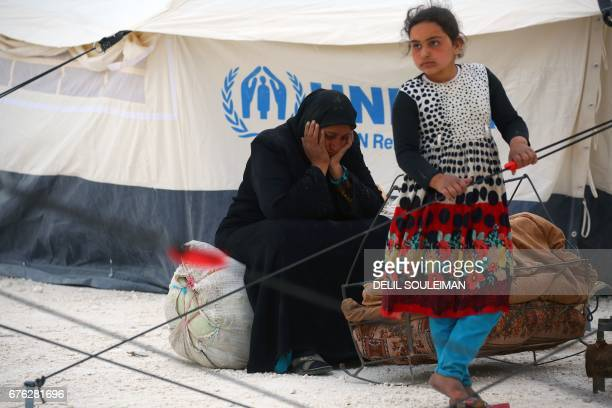 Displaced Syrians, who fled the countryside surrounding the Islamic State group stronghold of Raqa, arrive at a temporary camp in the village of Ain...