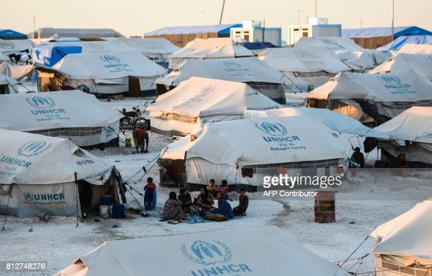 Displaced Syrians who fled the countryside surrounding the Islamic State group's Syrian stronghold of Raqa have dinner at a temporary camp in the...
