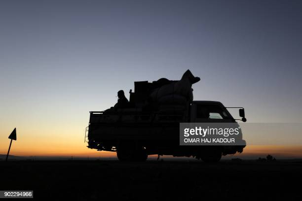 TOPSHOT Displaced Syrians who fled the fighting in Idlib province's southeastern town of Sinjar drive on a road in a rebelheld area near the city of...