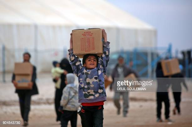 Displaced Syrians who fled their homes in Deir Ezzor city carry boxes of humanitarian aid supplied by United Nations Children's Fund at a refugee...