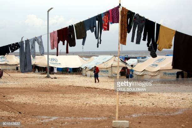 TOPSHOT Displaced Syrians who fled their homes in Deir Ezzor city walk around a refugee camp in Syrias northeastern Hassakeh province on February 26...