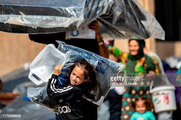 Displaced Syrians who fled their homes in the border town of Ras alAin receive humanitarian aid on October 12 in the town of Tal Tamr in the...
