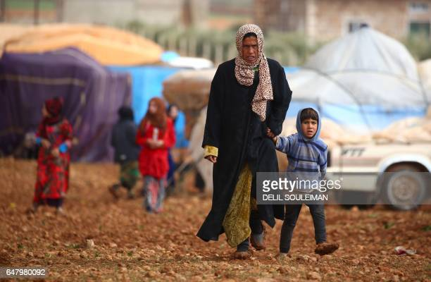 Displaced Syrians, who fled their hometowns due to clashes between regime forces and the Islamic State group, are seen in Kharufiyah, 18 kilometres...
