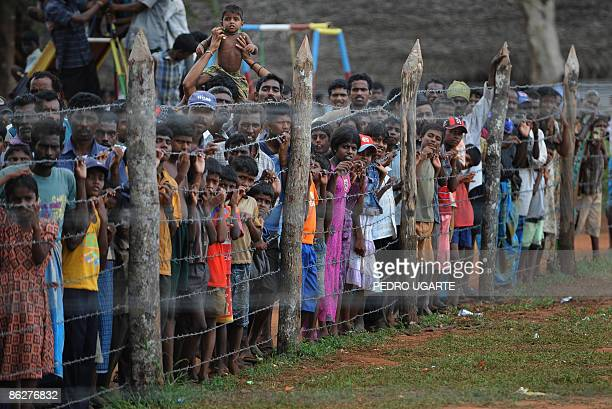 Displaced Tamil civilians watch as unseen French and British Foreign Ministers Bernard Kouchner and David Miliband arrive at Kadirgamh camp in...