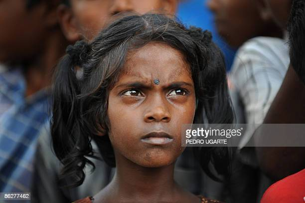 A displaced Tamil girl looks on as unseen French and British Foreign Ministers Bernard Kouchner and David Miliband arrive at Kadirgamh camp in...