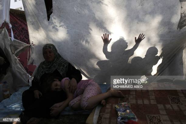 A displaced woman and a girl rest inside a makeshift tent outside which chilren are seen playing on July 27 2014 in the garden of AlShifa hospital in...