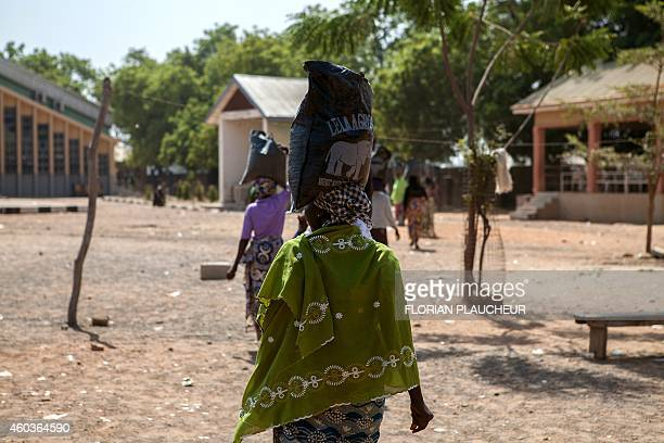 A displaced woman carries a sack of food aid received during a distribution at the Cathedral of Yola state capital of Adamawa on December 4 2014 Over...
