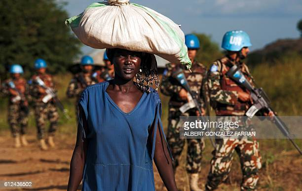 TOPSHOT A displaced woman carries goods as United Nations Mission in South Sudan peacekeepers patrol outside the premises of the UN Protection of...