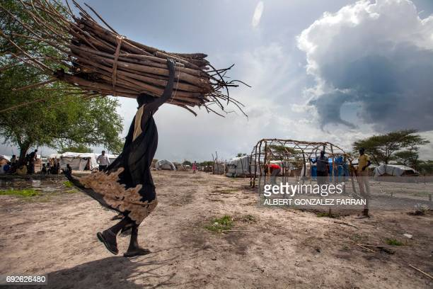 Displaced woman carries wood to build a new shelter in Aburoc, South Sudan on June 5, 2017. Government offensives on the West Bank of the Nile river...
