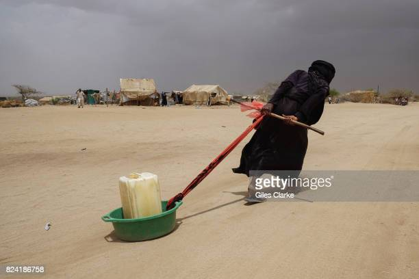 A displaced woman drags water back to her tent in Abs IDP camp located just 40 KM from the frontline to Saudi Arabia