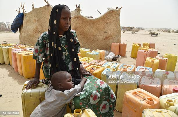 A displaced woman sits on a water can as she waits with her child to during a water distribute by agents from the UN System in a refugees camp of...