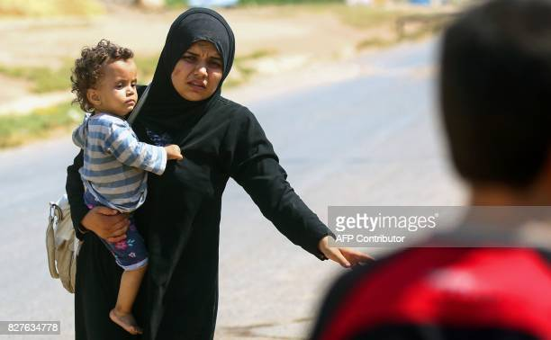 A displaced woman who fled from the Islamic State group's stronghold of Raqa carries a child in her hand as she arrives at the village of Hawi alHawa...