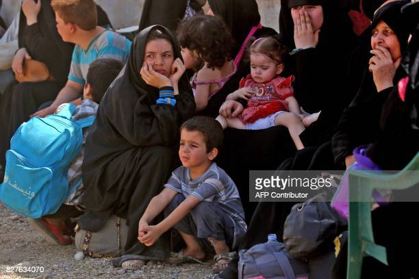 Displaced women and children who fled from the Islamic State group's stronghold of Raqa arrive in the village of Hawi alHawa less than two kilometres...
