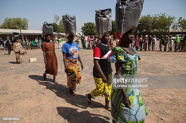 Displaced women carry sacks of food aid received during a distribution at the Cathedral of Yola state capital of Adamawa on December 4 2014 Over 15...