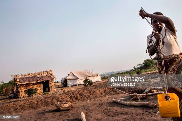 A displaced women pulls a bucket of water from a borehole in a relocation site in Mozambique on December 10 2015 Heavy rainfall in early 2015 caused...