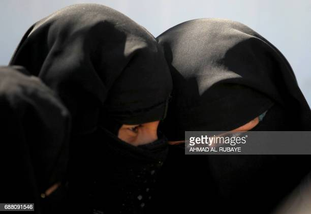 Displaced women stand in line to get food at the Hammam alAlil camp for internally displaced people south of Mosul on May 25 as government forces...