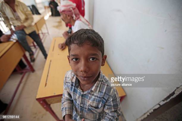A displaced Yemeni boy who fled his home in the wartorn port city of Al Hudaydah rests after arriving at a school as clashes intensify in western...
